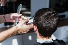 Perfect trim. Rear view close-up of young man getting haircut by hairdresser with electric razor. stock photos