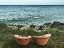 That is a perfect way to chill out. Two chairs put in front of water meant to relax royalty free stock photos