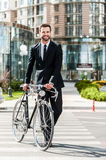 The perfect way to get to work. Full length of smiling young businessman rolling his bicycle while crossing the street Royalty Free Stock Photos