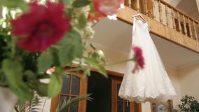 The perfect wedding dress with a full skirt on a hanger in the room of the bride with blue curtains stock footage
