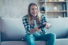 It is a perfect weekend for every man! Happy young guy is holdin. G gamepad and playing his favourite game Stock Images