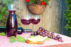 Perfect wine set for relaxed summertime enjoyment. Two glasses and decanter and bottle with homemade red wine, some grape, and cheese on table in garden on a Royalty Free Stock Image