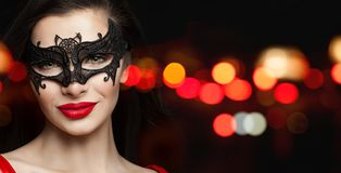 Perfect woman face in black carnival mask and red lips makeup on black background with abstract night glitter bokeh.  royalty free stock photography