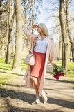 Perfect woman with flowers outdoors. Blonde female model Royalty Free Stock Photos