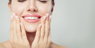 Perfect woman smile and manicured hand. French manicure and pink lipgloss makeup.  stock photos