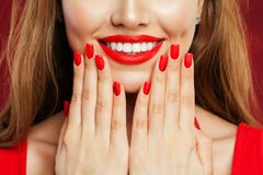 Perfect woman touching her face her hand with manicure. Makeup lips with red lipstick and red nail polish, beauty salon concept.  stock photo