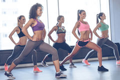 Perfect workout for girls. Beautiful young women with perfect bodies in sportswear exercising with smile while standing in front of window at gym Royalty Free Stock Photos