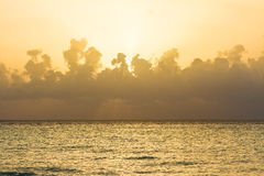 Perfect yellow sunset at the sea with puffy clouds Stock Photography