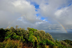 Perfecte regenboog over de oceaan bij Kaap Byron Stock Foto's