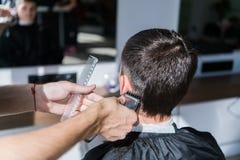 Perfecte versiering Achtermeningsclose-up die van de jonge mens kapsel door kapper met scheerapparaat krijgen stock afbeelding