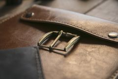 Close up of brown leather handmade handbag with bronze clasp on wooden table royalty free stock image