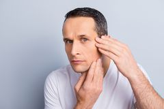 Perfection is a hard work even for men. Pampering, aging, oily,. Dry skin concept,  portrait of worried guy touching his cheek, examine, expertising face skin Stock Image