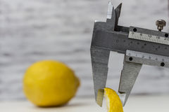 Perfectionism. Measuring a Lemon Slice with the use of a Vernier Caliper Royalty Free Stock Images