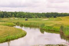 Perfectionnez la terre onduleuse avec l'herbe verte sur un champ de golf Photo stock