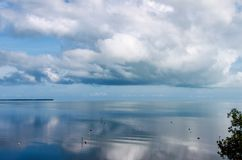 The perfectly calm ocean mirrors the clouds in the sky Royalty Free Stock Images
