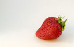 A perfectly cleaned strawberry with leaves isolated on the white background.  royalty free stock images