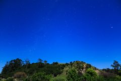 Star-filled sky and moonlit hill in the Southern Hemisphere. A perfectly clear night sky as seen from the Bay of Plenty, New Zealand. The view looks southwest royalty free stock images