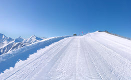 Perfectly groomed ski slope with mountains Stock Photography