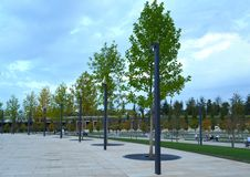 Trees in concrete in the Park. Perfectly maintained park with a concrete path in the accompanied by some benches surrounding the scene with a cloudy sky above it stock photo
