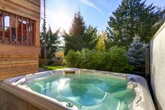 View of the back yard with hot tub for quiet relaxation. Perfectly manicured backyard boasts modern hot tub for quiet relaxation. Northwest, USA stock images