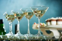 Perfectly polished martini glasses. Are standing on the blue background near candy-bar with different souffle and mousses Royalty Free Stock Images