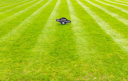Perfectly striped freshly mowed garden lawn with a warning sign. A beautiful green garden lawn that has just been mowed with an attractive pattern of stripes and royalty free stock photo