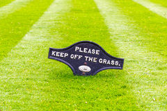Perfectly striped freshly mowed garden lawn with a warning sign. A beautiful green garden lawn that has just been mowed with an attractive pattern of stripes and stock photo