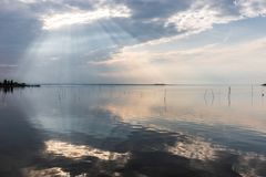 Perfectly symmetric and spectacular view of a lake, with clouds, sky and sun rays reflecting on water.  Stock Photo