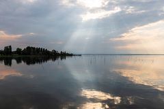 Perfectly symmetric and spectacular view of a lake, with clouds, sky and sun rays reflecting on water.  Royalty Free Stock Photo