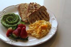 Perfekt frukost med rostat bröd, avokadot, ägget och bär royaltyfri fotografi