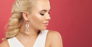Perfekt kvinna i halsband och örhängen för guld- kedja mot färgrik rosa väggbakgrund med kopieringsutrymme royaltyfria bilder