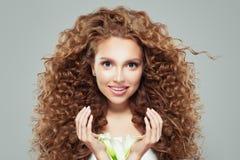 Perfekt kvinna med långt lockigt brunt hår, sund hud och liljablomman i hennes händer fotografering för bildbyråer