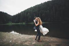 Perfekt parbrud, brudgum som poserar och kysser i deras bröllopdag Arkivbild