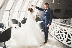 Perfekt parbrud, brudgum som poserar och kysser i deras bröllopdag royaltyfri foto