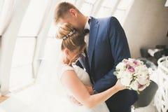 Perfekt parbrud, brudgum som poserar och kysser i deras bröllopdag royaltyfri bild