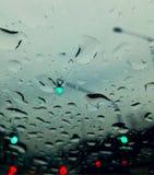 Perfekt regn tappar på exponeringsglaset av bilen Arkivfoton