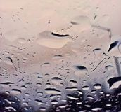 Perfekt regn tappar på exponeringsglaset av bilen Royaltyfria Bilder