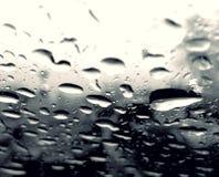 Perfekt regn tappar på exponeringsglaset av bilen Arkivbilder