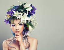 Perfekt ung kvinna med den blom- frisyren Arkivbild