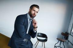 Perfekt van vid blick Den stiliga unga affärsmannen ser bort, medan stå i hans moderna kontor arkivbilder