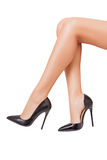 Perfekta ben i svarta skor över vit bakgrund Arkivfoto