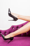Perfekta ben i svarta skor på den lyxiga soffan Arkivbild