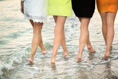 Perfekta kvinnlig lägger benen på ryggen på bakgrunden av havet Fyra charmiga kvinnor går nära det blåa havet härlig damtoalett fotografering för bildbyråer