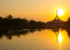 Perfekta reflexioner av iconic byggnad på vattendammet på Suan Luang Rama IX parkerar, gränsmärket av Thailand med härlig solnedg royaltyfri bild