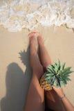 Perfekte Ferien Junge Frau auf dem Strand von Formentera-Insel Weibliche Beine mit Ananas auf dem Strand am sonnigen Tag Vertikal Lizenzfreies Stockfoto