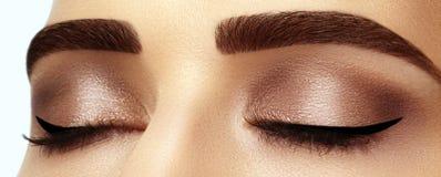 Perfekte Form von Augenbrauen, von braunen Lidschatten und von langen Wimpern Nahaufnahmemakroschuß des rauchigen Augenantlitzes  stockfotografie