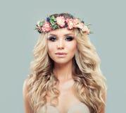 Perfekte junge Frau mit dem langen gewellten Haar und den Blumen Lizenzfreie Stockfotografie