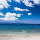Perfekte Kiesel setzen und blauer Himmel mit Wolken auf den Strand Stockfotografie