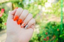 Perfekte Maniküre und natürliche Nägel Attraktives modernes Nagelkunstdesign orange Herbstdesign lange gut-gepflegte Nägel lizenzfreies stockfoto
