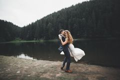 Perfekte Paarbraut, Bräutigam, der in ihrem Hochzeitstag aufwirft und küsst Stockfotografie